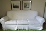 Mitchell Gold leather sofa shown with slip cover