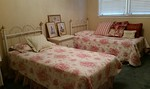Pair of clean twin beds with headboards, perfect for a guest room or child's room.
